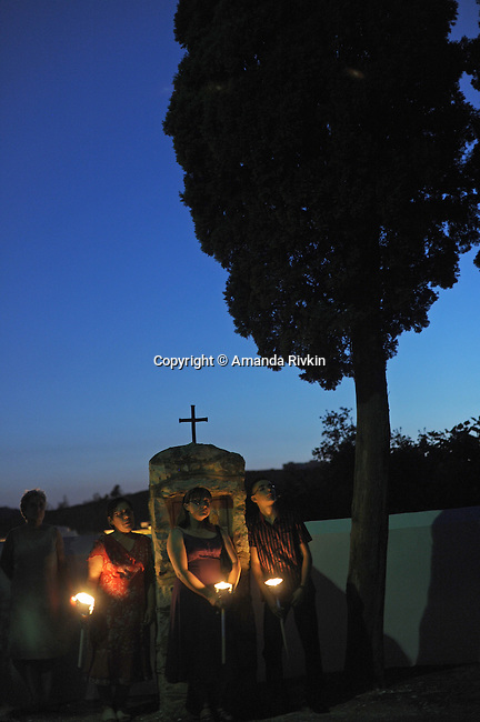 Villagers hold candles after arriving at the cavalry and cemetery following a procession during the municipal fiestas in Costur, Spain on August 16, 2009.