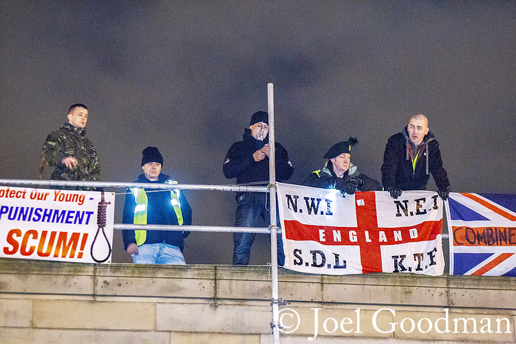 """© Joel Goodman - 07973 332324 . 03/03/2012 . Heywood , UK . Following a National Front demonstration in nearby Heywood, a rooftop demonstration by the """"North West Infidels"""" and the """"Combined Ex Forces"""" is held on Bury Town Hall. Police said the group had climbed up scaffolding at the side of the Town Hall building to gain roof access. Protesters have affixed banners stating """"Hang paedo scum"""" and various nationalist slogans . Photo credit : Joel Goodman"""