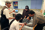 "Cris L'ariste an Israeli  medical clown who works in Hadassah and he is a member of a group call ""Dream Doctor"", distracts a Palestinian boy as a nurse introduces a line on the vein with the help of the parents to take a blood test in the Oncology Day Care unit at Hadassah Ein Karem hospital. Photo by Quique Kierszenbaum."