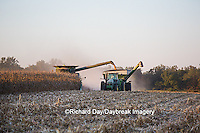 63801-06616 John Deere combine harvesting corn while unloading corn into wagon, Marion Co., IL
