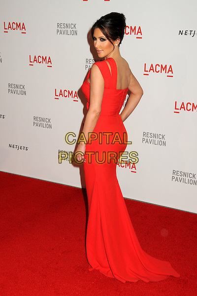"KIM KARDASHIAN .at LACMA's ""The Unmasking"" The Lynda & Stewart Resnick Exhibition Pavilion Opening Gala at The Los Angeles County Museum of Art in Los Angeles, California, USA, September 25th 2010..full length long maxi dress red one strap  shoulder hand on hip back rear behind side .CAP/ADM/BP.©Byron Purvis/AdMedia/Capital Pictures."