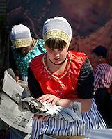 Tijdens Urkerdag lopen de bewoners in klederdracht. Meisje pakt vis in