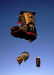 A hot air balloon shaped like a boot floats above Albuquerque, New Mexico during a hot air balloon festival.
