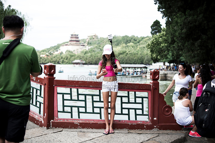 A Chinese girl takes a selfie with a GoPro camera on the lake of the Summer Palace in Beijing, China, July 21, 2014. <br /> <br /> Smartphones are an essential tool of Chinese ordinary life. Everywhere in China, people use them to take pictures to share online, to talk and chat, to play videogames, to get access to the mainstream information, to get connected one each other. In the country where the main global social media are forbidden - Facebook, Twitter and Youtube are not available  -, local social networks such as WeChat have a wide spread all over the citizens. The effect is an ordinary and apparently compulsive way to get easy access to digital technology and modern way of communication. <br /> A life through the display. Yes, We Chat.<br /> <br /> © Giorgio Perottino