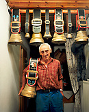 SWITZERLAND, Motiers, George Montandon stands in the kitchen of his home holding a cow bell that was given to him by a friend for his 45th wedding anniversary, Jura Region