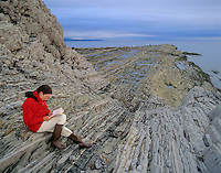Woman sites amid layers of upturned sedimentary rocks at Green Point in Gros Morne National Park, Newfoundland, Canada, AGPix_0518..