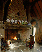 A massive brick fireplace at one end of the stone-flagged hall of a restored English tithe barn