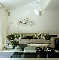 The black and white checked sofa is accented with dyed-green fur and leaf print cushions