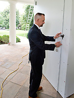 An unidentified Secret Service agent locks the protective outer door leading to the Oval Office in the White House West Wing in Washington, DC as it is undergoing renovations while United States President Donald J. Trump is vacationing in Bedminster, New Jersey on Friday, August 11, 2017.  <br /> CAP/MPI/CNP/RS<br /> &copy;RS/CNP/MPI/Capital Pictures