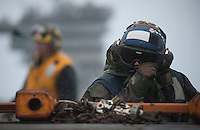 120507-N-DR144-102 PACIFIC OCEAN (May 7, 2012) Airman Leah Vasquez, assigned to the Air Department's V-1 Division, braces against rain while manning a tow tractor to reposition aircraft on the flight deck aboard the Nimitz-class aircraft carrier USS Carl Vinson (CVN 70). Carl Vinson and Carrier Air Wing (CVW) 17 are deployed to the 7th Fleet area of operations. (U.S. Navy photo by Mass Communication Specialist 2nd Class James R. Evans/Released)