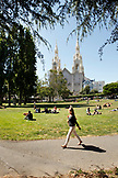 USA, California, San Francisco, a woman walks by people sitting on the lawn and enjoying the afternoon, Washington Square Park