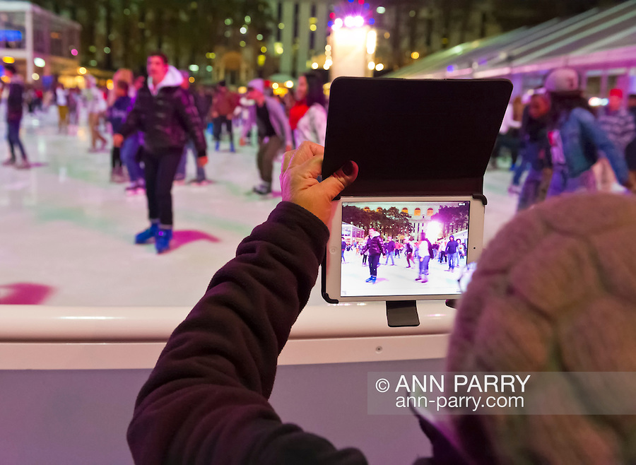 Manhattan, New York, U.S. 9th November 2013. Visitors uses iPad tablet to take photo of ice skaters, at Winter Village skating rink at Bryant Park that night,