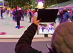Manhattan, New York, U.S. 9th November 2013. Visitors uses iPad tablet to take photo of ice skaters, at Winter Village skating rink at Bryant Park that night,