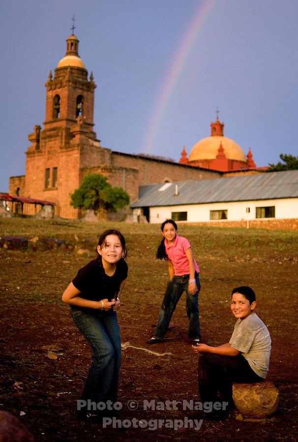 Kids play as a rainbow sits over the San Francisco Javier de Cerocahui church in the small village of Cerocahui, about 8 miles from the Bahuichivo train station, Thursday, June 19, 2008. Carocahui, located at the edge of Urique Canyon, is nestled in mountains filled with roaming apple orchards and small streams and was developed as a main stopping point for Jesuit priests in the 1600s..PHOTOS/ MATT NAGER