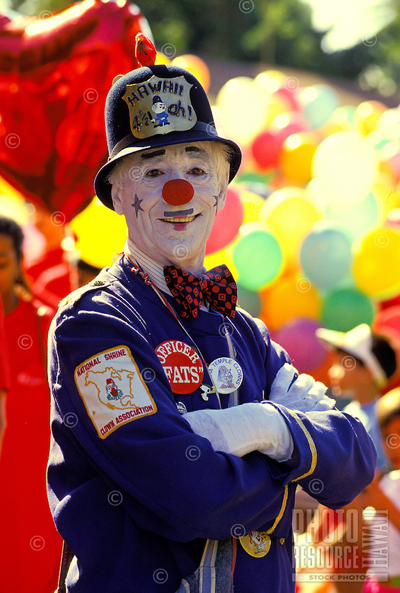 Officer Fats, a Shriner clown stands with arms folded with a background of multicolored balloons at the annual Aloha Week Parade on Oahu.