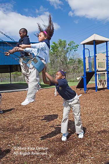 African American seven year old girl in uniform pushes minority female in swing on school ground with black boy in other swing on sunny day
