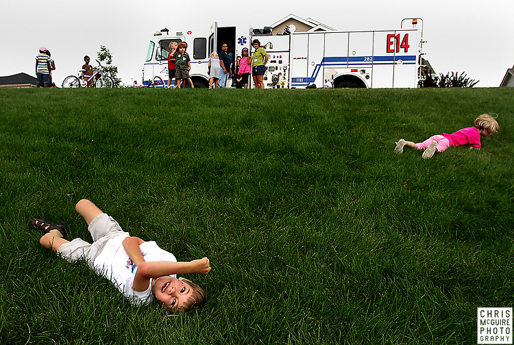 Caleb Buonamici, 6, left, and Taisia Mills, 5, roll down a hill during the Westchase subdivision Neighborhood Night Out in southeast Fort Collins on Tuesday, August 5, 2008.