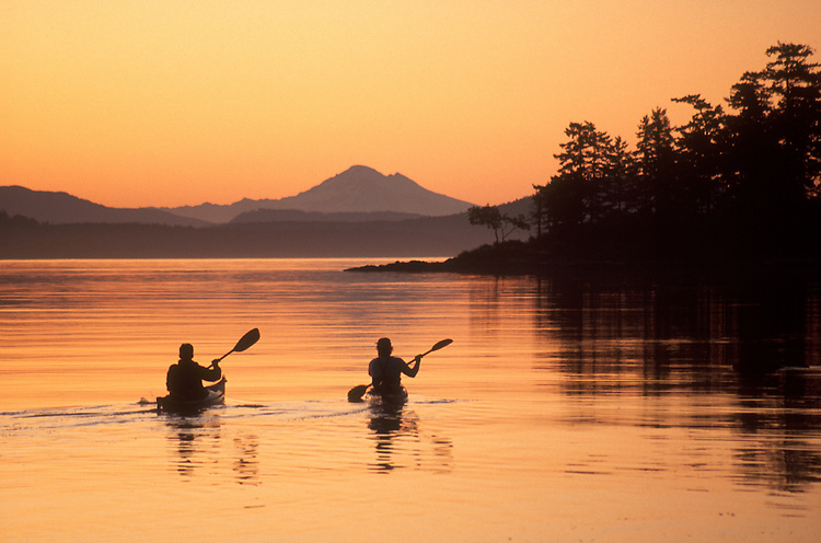 Sea Kayaking, San Juan Islands, Sea kayakers paddle into sunrise off D'Arcy Island, the San Juan Island and Mount Baker in the distance,.