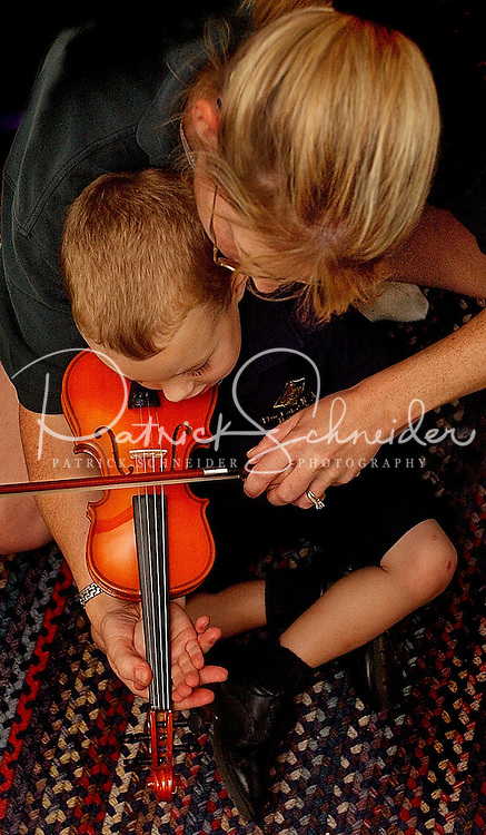 A mother teaches her young son how to play a child-size violin.