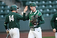 Catcher Scott Combs (35) of the Michigan State Spartans is congratulated by Andrew Morrow (14) after throwing out a runner at second in a game against the Merrimack Warriors on Saturday, February 22, 2020, at Fluor Field at the West End in Greenville, South Carolina. Merrimack won, 7-5. (Tom Priddy/Four Seam Images)