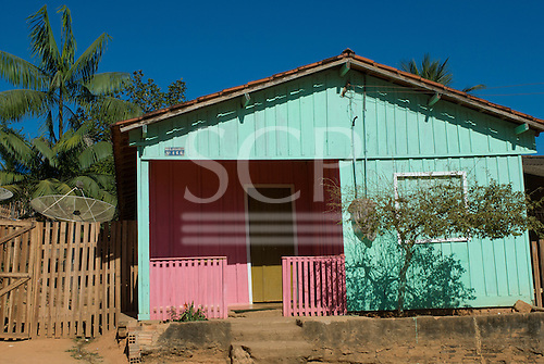 Pará State, Brazil. São Félix do Xingu. Wooden house painted in bright pastel green and pink with satellite television dish.