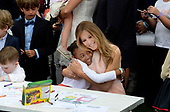 First Lady Melania Trump hugs a girl as they make cards for members of the military at the annual Easter Egg roll on the South Lawn of the White House in Washington, DC, on April 17, 2017. <br /> Credit: Olivier Douliery / Pool via CNP