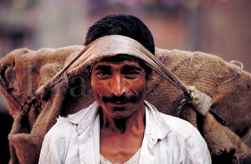 Portrait of a smiling man carrying large burlap bag by tumpline; full face; head and shoulders. Kathmandu, Nepal.