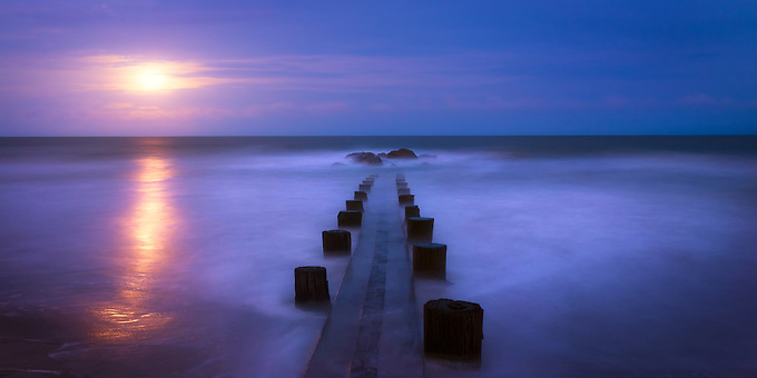 On a calm evening, the moon rises as the incoming tide washes over an old jetty on the Atlantic Coast.