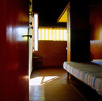 A view into a monastic plywood-clad cabin which is furnished with such essentials as a bed, a narrow wardrobe and a basin