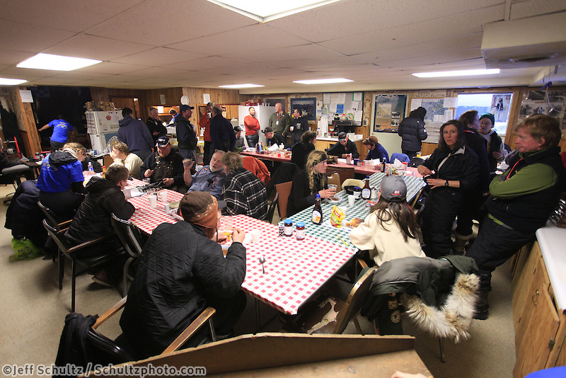 Visitors, mushers, volunteers and residents hang out inside the community center at the Takotna checkpoint on Wednesday evening during Iditarod 2011.
