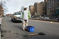 Jerome Whitaker fills potholes with asphalt while working for the Boston Public Works Department in Boston, Massachusetts, USA, on April 12, 2012. The city uses a computer system to track public complaints and record work done by city crews to mitigate these complaints.  A supervisor or inspector photographs before and after pictures of the work in addition to making notes about the work done.