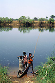 Chambesi River, Zambia. Children in a dugout canoe with fishing rod at the river bank.
