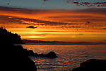 Beautiful dramatic dark amber glowing sky sunset scenery on the Pacific ocean coast with dark rocky shores in Nanaimo, Vancouver Island, BC, Canada.