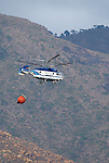 Kamov fire fighting helicopter carrying water ballon, assisting in fighting forest fire. Estepona, Costa del Sol, Andalucia Spain.