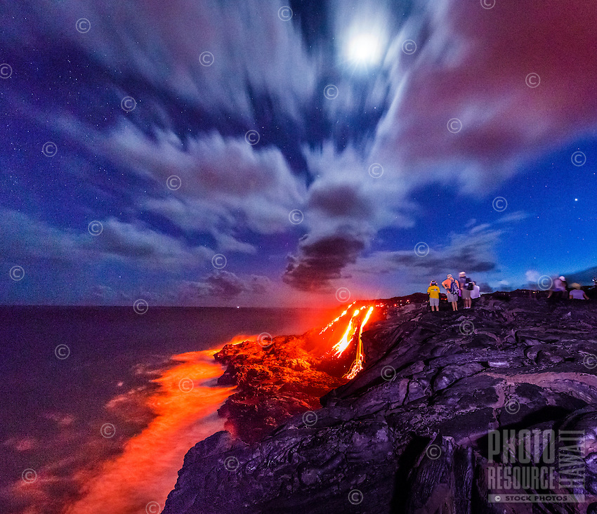 Visitors view the spectacular sight of lava flowing down a cliff and into the ocean as the moon rises, Hawai'i Volcanoes National Park, Hawai'i Island.