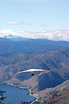 A hang glider pilot soars toward the Columbia River as he seeks thermals that will lift him to cloud base. Hang glider pilots travel to Lake Chelan to fly Chelan air for its famous long distance flight possibilities