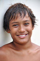 A local boy smiles after he and his friends repeatedly jumped into the river from the Haleiwa bridge on O'ahu's North Shore.