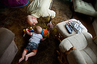 Fred Bermont plays with daughter Elyse Bermont (in tent, not pictured, age 2.5) and son Dylan Bermont (age 9 months) in their home in Lexington, Massachusetts, USA, before he goes to work and drops the kids off at day-care on June 9, 2014. Bermont is the father of two children and shares parenting duties with his wife, Jen Bermont. Fred usually takes care of the morning routine, including feeding, dressing, and dropping the kids off at day-care, and Jen picks them up and watches over them in the afternoon. Fred is a Senior Clinical Standards Specialist at Shire, a pharmaceutical company with headquarters in Lexington.