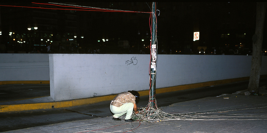 A woman connects one more electrical wire to an already overburdened light post.  She does this provide her christmas stall with free electricity.  this common practice in mexico is called ¨diablitos¨ which translates as little devil.