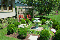 English formal style garden scene with house, covered garden bench swing and trellis, double bird bath water fountain, Buxus boxwood trimmed into globes, Leucanthemum Shasta Daisies, Vinca, lawn grass, blue sky and clouds on sunny summer day, trees, beautiful backyard landscaping