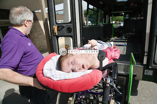 Staff wheeling physically disabled child into ambulance,