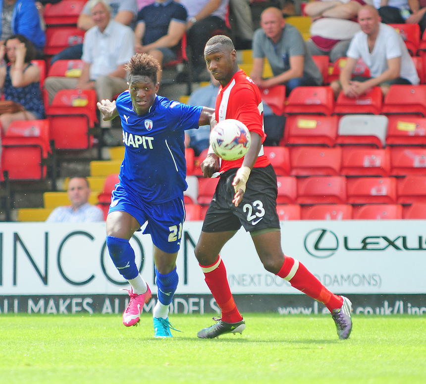 Chesterfield's Armand Gnawduellet vies for possession with Lincoln City's Nat Brown<br /> <br /> Photographer Chris Vaughan/CameraSport<br /> <br /> Football - Friendly - Lincoln City v Chesterfield - Saturday 19th July 2014 - Sincil Bank Stadium - Lincoln<br /> <br /> &copy; CameraSport - 43 Linden Ave. Countesthorpe. Leicester. England. LE8 5PG - Tel: +44 (0) 116 277 4147 - admin@camerasport.com - www.camerasport.com