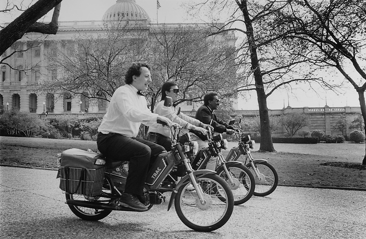 Kaya Kazmirci, Adrian Niu, Melaku Mengistu on Track mopeds with food inside baskets on April 8, 1990. (Photo by Laura Patterson/CQ Roll Call via Getty Images)