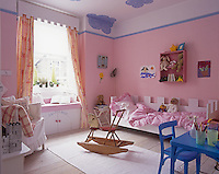 A child's bedroom is decorated with pink gingham check wall covering, matching bedding and window seat.