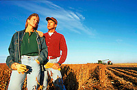 Male and female farmers in soybean field during harvest season.
