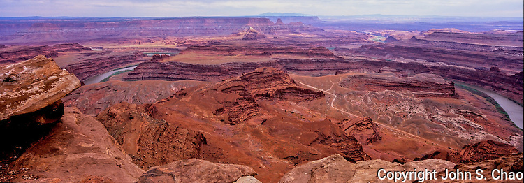 Panoramic view towards Canyonlands National Park with Colorado River bend from Dead Horse Point State Park, Utah. Potash Road/Shafer Canyon road in right foreground.