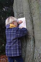 Junge, Kinder, Kind machen Abdruck von Rinde, Baumrinde, Baum-Rinde, dazu wird ein Blatt weißes Papier an den Stamm eines Baumes gelegt und mit Wachsmalstiften abgerubbelt. Unterschiedliche Rindentypen ergeben unterschiedliche Abdrücke
