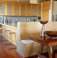The large polished concrete banquette in the kitchen-diner of a New York loft is integral to the worktop behind it