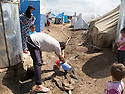Iraq 2013 .In the unofficial camp, water is supplied every 4 days to fill the tanks.A refugee collects water leaking from the pipe .  .Irak 2013 .A cote du camp de Domiz, le camp officieux des nouveaux arrivants. Tous les 4 jours distribution d'eau pour remplir les reservoirs. Un refugie recupere de l'eau fuyant le long d'une canalisation