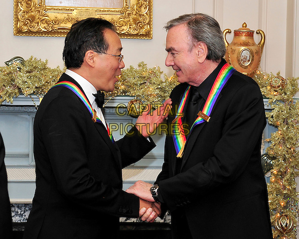 Yo-Yo Ma and Neil Diamond .The 2011 Kennedy Center Honors, shares some thoughts as they wait to pose for a group photo following a dinner hosted by United States Secretary of State Hillary Rodham Clinton at the U.S. Department of State in Washington, D.C., USA..December 3rd, 2011.half length black suit tuxedo glasses side profile shaking hands.CAP/ADM/RS.©Ron Sachs/CNP/AdMedia/Capital Pictures.